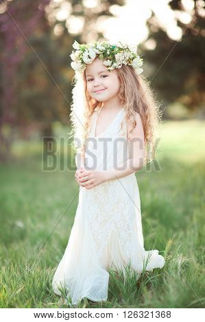 Smiling baby girl 4-5 year old wearing wreath with flowers outdoors. Looking at camera. Childhood.