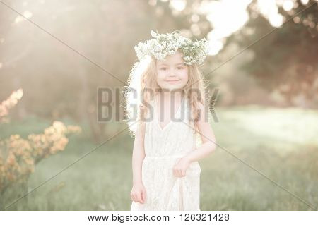 Smiling kid girl 4-5 year old wearing stylish white dress and flower wreath outdoors. Looking at camera. Sunny day.