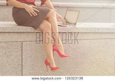 Close-up picture of beautiful woman's lags sitting on concrete brick. Lady in high heels working with laptop computer outdoors. Toned image.