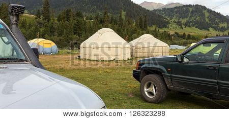 Two Off Road Vehicles Arrived to Remote Shepherd Village with Traditional Mongol Yurts in Mountain Landscape