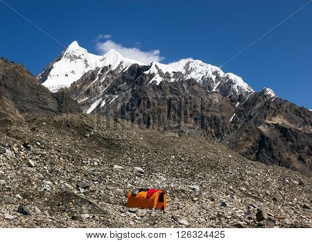 Base Camp of High Altitude Expedition at Mountains with Snow and Ice Summit Orange Bivouac with Sleeping Bags Drying on Roof of It