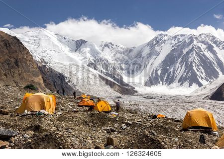 Many Orange Tents Located on Side Rock Moraine of Glacier in Severe Snow and Ice Peaks Valley