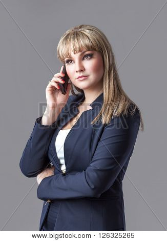Young business woman talking on a cell phone in a suit. A woman looking down. Isolated gray background