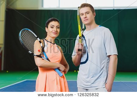 Two Happy smiling Tennis Players posing indoor.