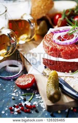 Raw Ground beef meat Burger steak cutlets with seasoning,vegetables and beer on vintage wooden boards