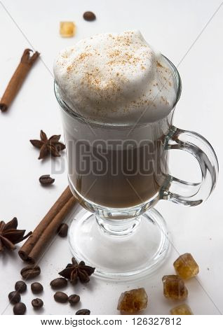 hot Cup of coffee with whipped milk foam on the white isolated background with cinnamon sticks stars of anise and caramel sugar. The idea for the menu and the coffee shop. Cappuccino hot.