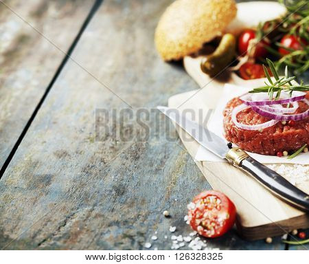 Raw beef burger for hamburger with vegetables on wooden table