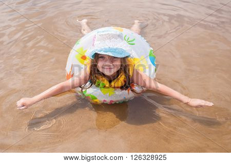 Little Girl In The Shallows Lying On His Stomach In The Inflatable Ring Outstretched Arms And Legs