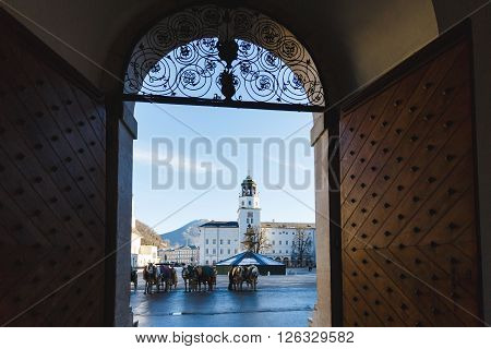 Salzburg Austria - January 07 2016: View of the horse carriage on the Residence square through the arch