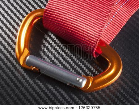 Orange carabiner with red nylon on a graphite background