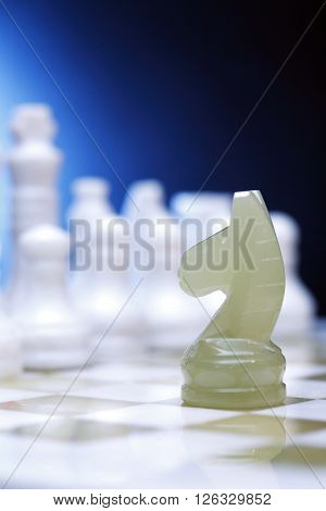 Chess horse made from Onyx on board against blue background