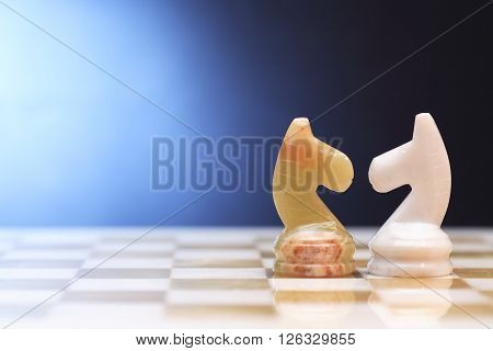 Pair of chess horses made from Onyx on board against blue background