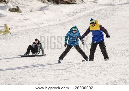 Dombay, Russia - February 7, 2015: The Instructor Teaches How To Ski On Snow Downhill Ski Training O