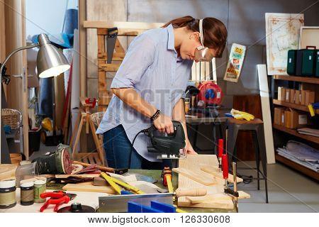 Woman working in workshop, using top handle jigsaw.