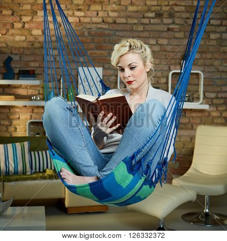 Blonde woman resting and reading in hammock like chair.