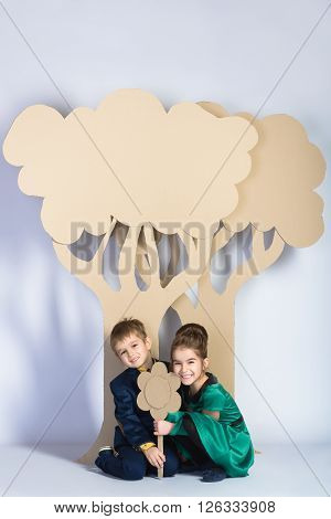 Love concept. Couple of kids. boy and girl with  cardboard trees.