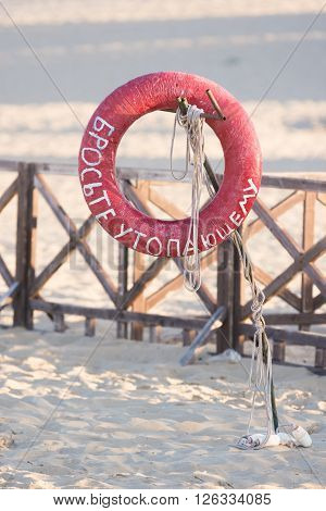 Lifebuoy Throw A Drowning Man With A Sign Hanging On A Rusty Metal Stick On The Sandy Beach