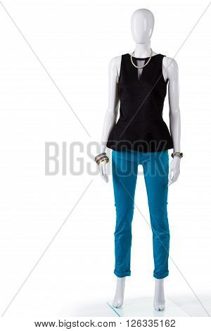 Black top with narrow v-neck. Female mannequin wearing black top. Dark top and turquoise pants. Outlet shop's summer sale.