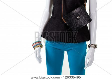Black top and vintage handbag. Small retro purse on mannequin. Turquoise pants with black bag. Selection of girl's trendy accessories.