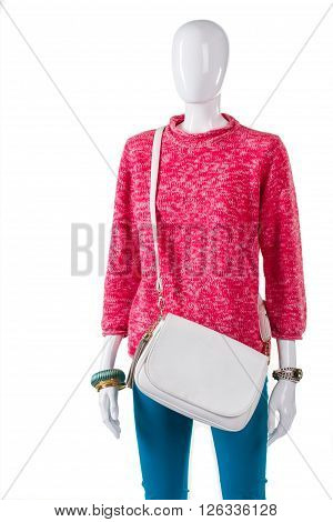 Pink sweater and white purse. Mannequin in outfit with bag. Girl's fashionable warm garment. Seasonal discounts in local boutique.