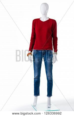 Red pullover and blue jeans. Female mannequin wearing red sweater. Autumn apparel on store showcase. Discounts for new merchandise.