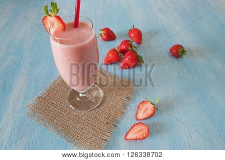 Strawberry healthy milkshake on blue wooden blackground. Strawberry Helthy Smoothie.