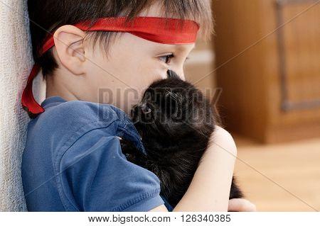 Toddler boy hugging little black newborn kitten