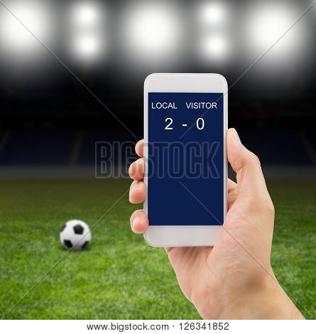 betting man through his smart phone in a stadium under the bright focuses