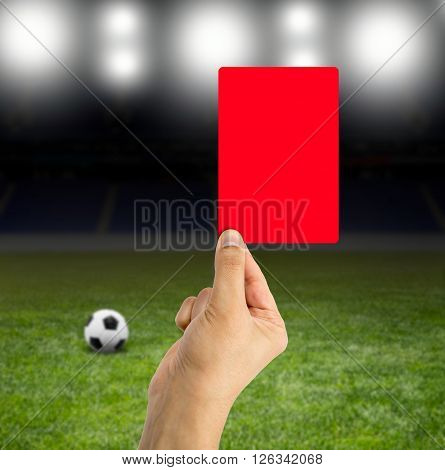 Football referee showing you the red card in a stadium under the bright focuses