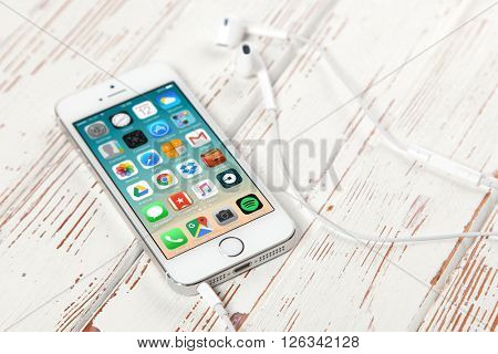 WROCLAW, POLAND - APRIL 12, 2016: Apple iPhone SE smartphone with main menu on screen