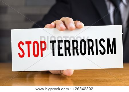 Stop terrorism message on white card and hold by businessman