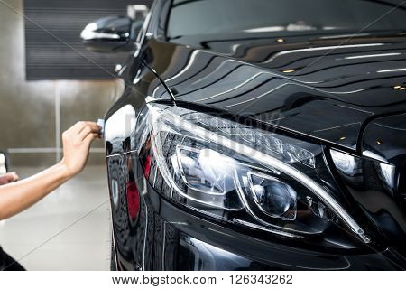 Car detailing series : Closeup of hand coating black car paint