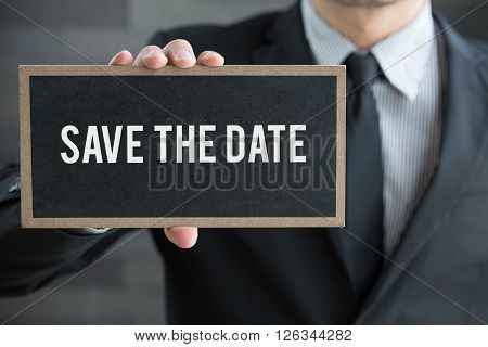 Save the date message on blackboard and hold by businessman