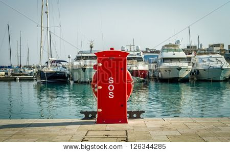 LIMASSOL, CYPRUS - SEPTEMBER 7: Red safety hydrant station, fire extinguisher cabinet and lifebuoy holder, in Limassol marina, Cyprus on September 7, 2015
