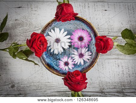 Red Roses And Gerbera Flowers On Wooden Table