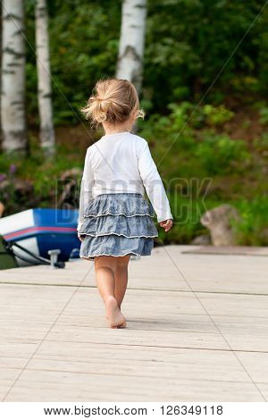Child walking barefoot on pier, back view