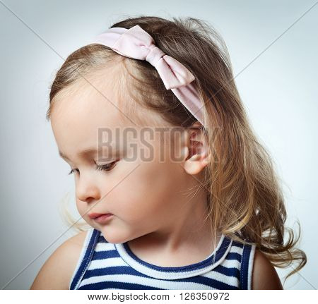Portrait of cute little girl looking down over gray background