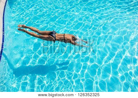 Woman jumping into the swimming pool.