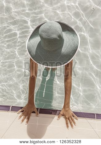 Woman in sun hat in the swimming pool. Top view. Vintage style.