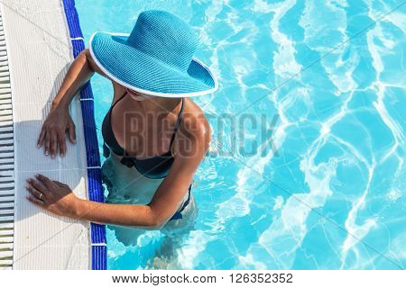 Woman in sun hat in the swimming pool. Top view.