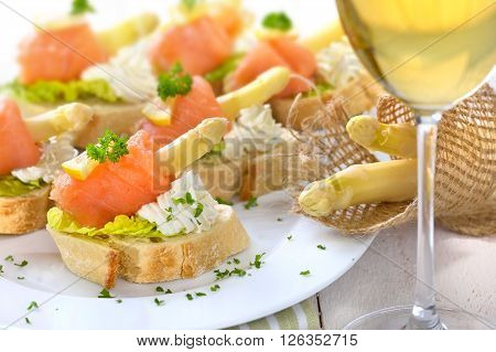 Delicious canapes with German white asparagus, cream cheese with herbs, smoked salmon on Italian ciabatta bread with lettuce leaves, served with a glass of white wine