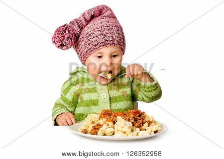 Cute child eating pasta, isolated over white