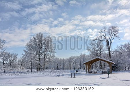 A snowy winter scene at a park in Toledo Ohio with the snow clinging to the trees and a pretty partly cloudy sky.
