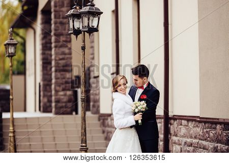 Portrait of a bride and groom lovely standing on the city street near the streetlight holding hands