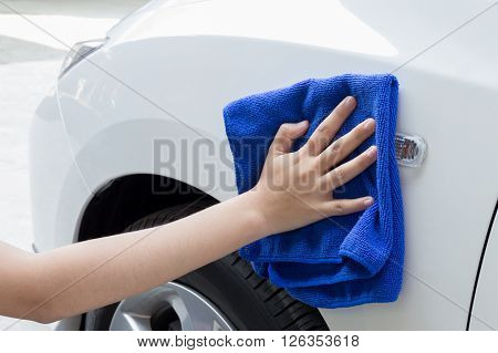 Concept of Woman cleaning car using microfiber cloth.