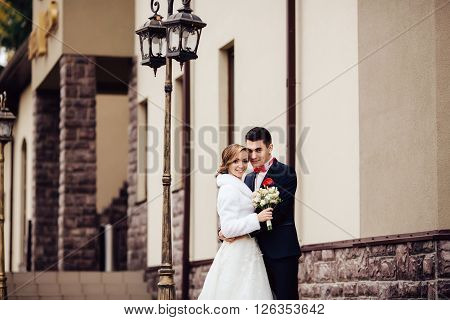 Portrait of a bride and groom standing on the city street near the streetlight and lovely hugging