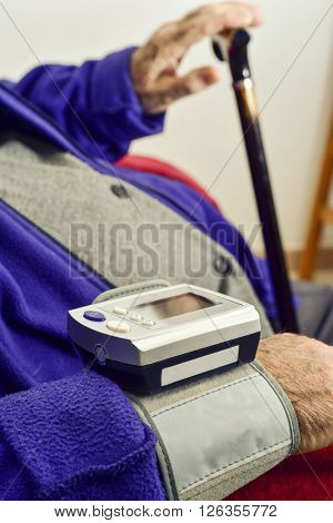 measuring the blood pressure to an old caucasian man with an electronic sphygmomanometer