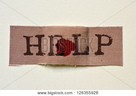 closeup of a fabric adhesive bandage with a blood stain and the text help, on an off-white background