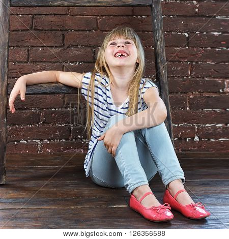 Girl 6 years old in jeans and a vest sits on the floor next to a brick wall and filled with laughter