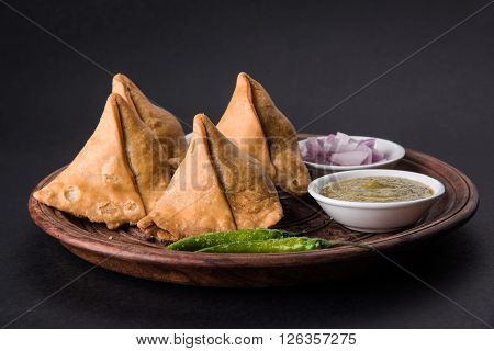 samosa snack with imli chutney or tamarind sauce, onion and green fried chili, served in a wooden plate